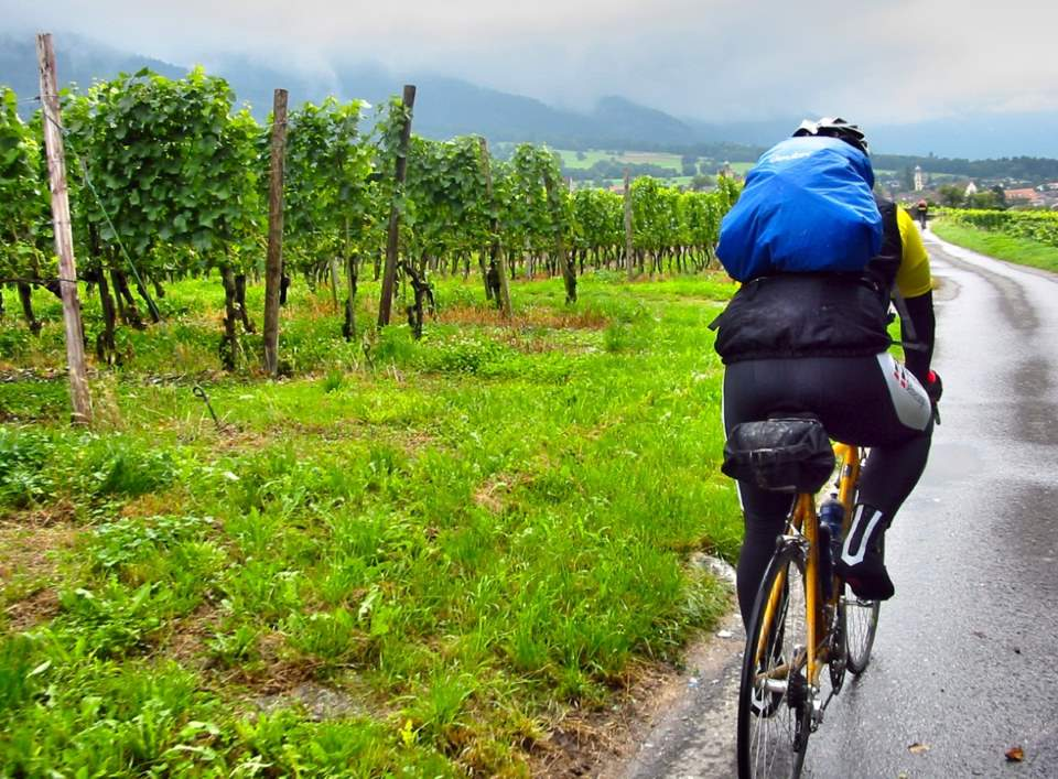 Tips for a Cycling Holiday in New Zealand - Cyclist riding in the rain with a backpack